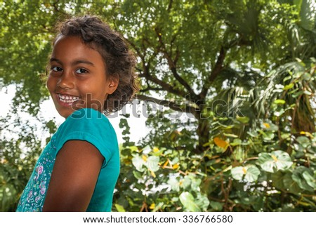 Beautiful young female girl with curly hair wearing a turquoise t-shirt.  Portrait of happy female child in front of green background, pefect for family blogs and magazines - stock photo