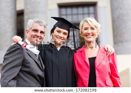 beautiful young female graduate with parents at ceremony - stock photo