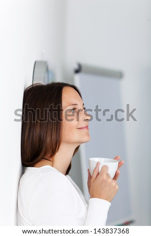 Beautiful young female having a cup of coffee while thinking about something and smiling - stock photo