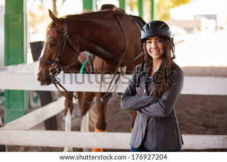Beautiful young female jockey standing next to her horse at the track - stock photo