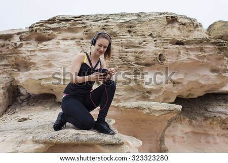 Beautiful young female jogger enjoying rest after workout while chatting on her mobile phone sitting on stone rock,attractive fitness woman choosing song in play list for listen to music in headphones - stock photo