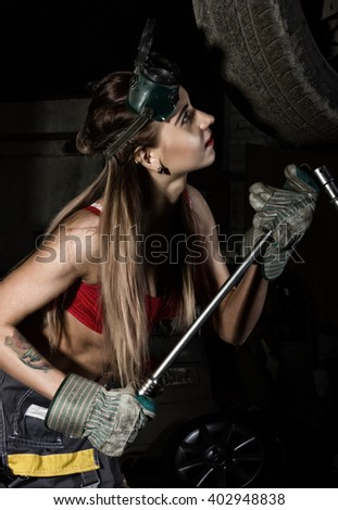 Beautiful young female mechanic inspecting car in auto repair shop. girl mechanic in overalls changes a wheel on a car in garage. Sexy mechanic - stock photo