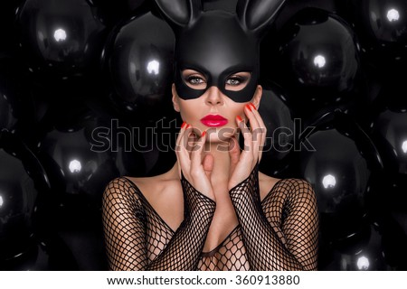 beautiful young female model in a black carnival mask, rabbit ears standing against the black balloons and sensually looks at the camera, wearing bodystocking dress with mesh and amazing makeup - stock photo