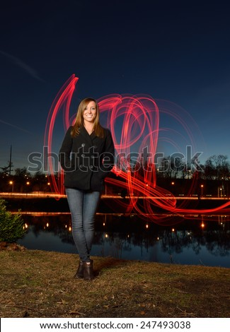 Beautiful young female model with light painting behind her - red light streaks