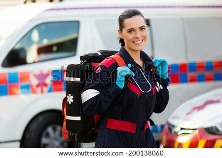 beautiful young female paramedic carrying lifepack in front of ambulance - stock photo