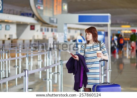 Beautiful young female passenger at the airport with take away coffee - stock photo