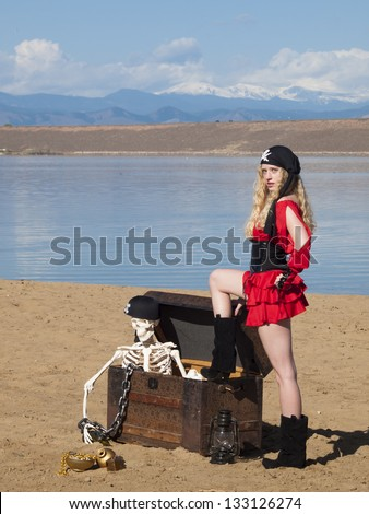 Beautiful young female pirate in red dress. - stock photo