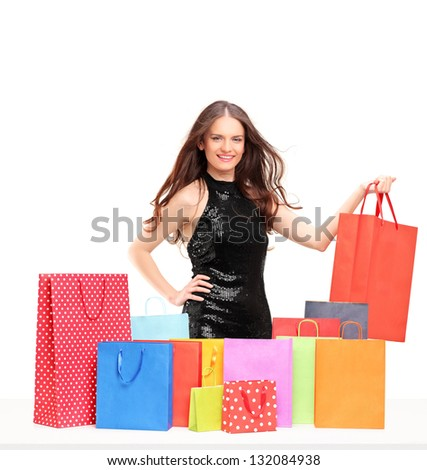 Beautiful young female posing with colorful shopping bags isolated on white background