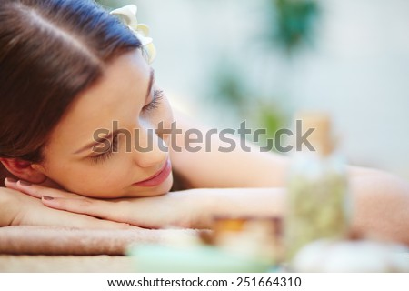 Beautiful young female relaxing in spa salon - stock photo