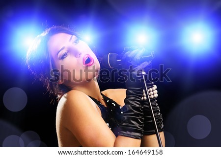 Beautiful young female singer in black dress singing on a stage