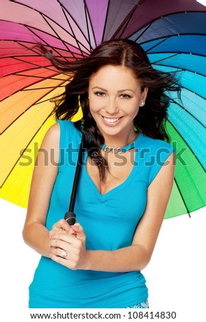 Beautiful young female standing under rainbow umbrella against white background - stock photo