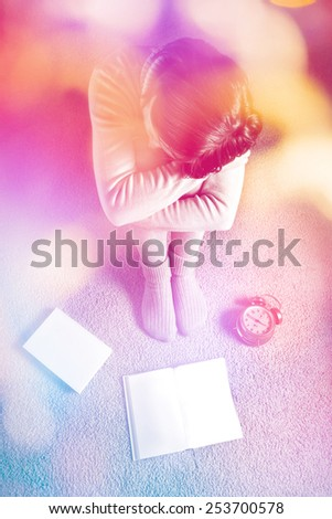 Beautiful young female student sitting on floor and daydreaming. - stock photo