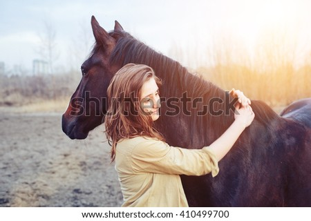 Beautiful young female walking and hugging with her brown horse outdoor - stock photo
