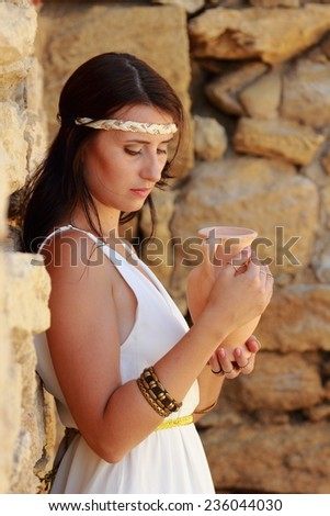 Beautiful young female wearing white dress in antique style  - stock photo