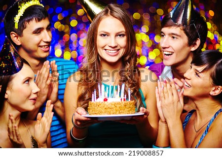 Beautiful young female with birthday cake looking at camera, her friends applauding