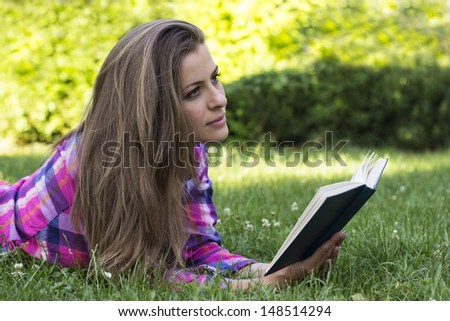 Beautiful young female with book in the hands, in the park