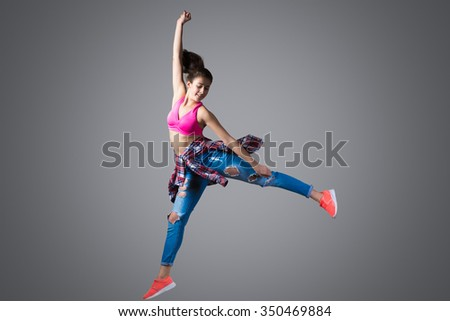 Beautiful young fit modern hip-hop dancer woman working out wearing torn jeans, leap high with joy, studio, gray background, full length - stock photo