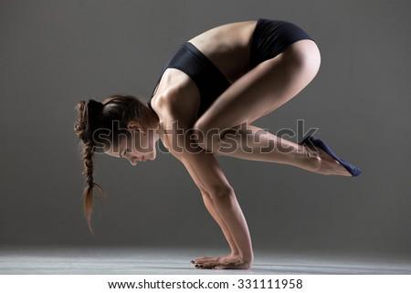 Beautiful young fit woman doing sport exercises, handstand yoga asana, Crane (Crow) Posture, Bakasana (Kakasana), full length, side view, studio shot on gray background - stock photo