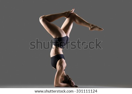 Beautiful young fit woman doing sport exercises, variation of supported headstand posture, salamba sirsasana with stag legs, full length, side view, studio shot on gray background