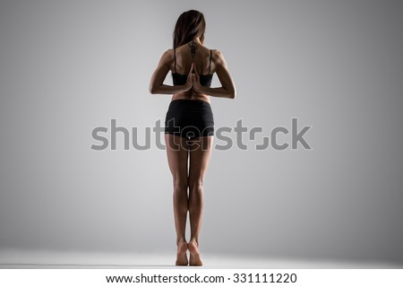 Beautiful young fit woman in sportswear doing exercises for spine, shoulders, wrists, standing on tip toes, holding Namaste gesture behind the back, full length, rear view, studio, gray background - stock photo