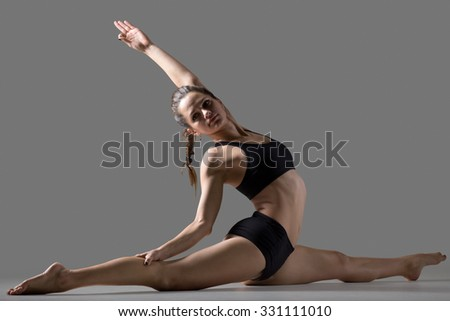Beautiful young fit woman in sportswear doing sport exercise, sitting in splits, variation of Monkey posture, Hanumanasana, side view, studio, gray background - stock photo