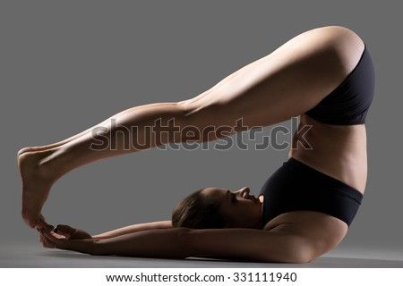 Beautiful young fit woman in sportswear shorts doing sport exercises, variation of Halasana, Plough (Plow) posture, Yin Yoga Snail Pose, full length, side view, studio image on gray background - stock photo