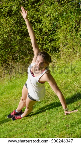 beautiful young fitness woman doing exercise in countryside