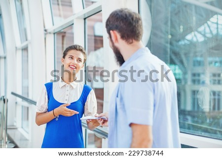 Beautiful young flight attendant checking documents in airport - stock photo