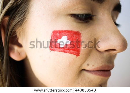 Beautiful young football fan woman with painted swiss flag on face closeup - stock photo