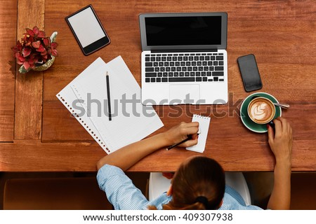 Beautiful Young Freelancer Woman Using Laptop Computer Sitting At Cafe Table. Happy Smiling Girl Working Online Or Studying And Learning While Using Notebook. Female Writing And Taking Notes On Paper. - stock photo