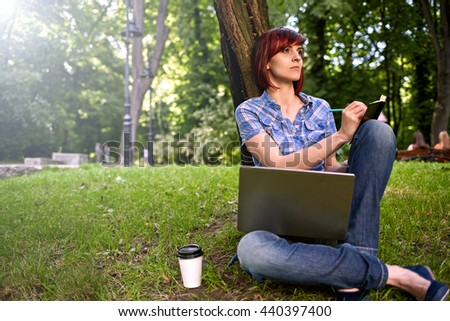 Beautiful young freelancer woman using laptop sitting on the grass in the park.Happy smiling girl working on line.Studying and learning using notebook computer.Freelance work,business people concept. - stock photo