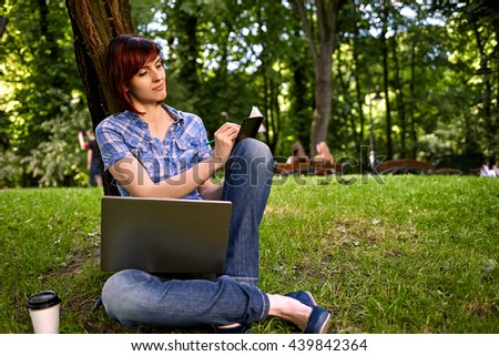 Beautiful young freelancer woman using laptop sitting under the tree in the park.Happy smiling girl working on line.Studying and learning using notebook computer.Freelance work,business people concept