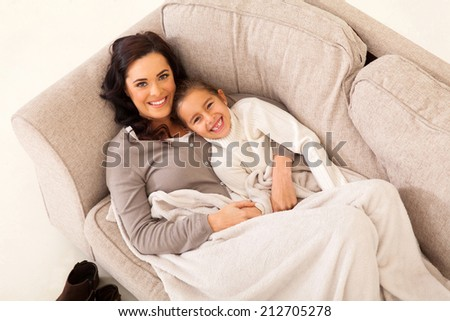 beautiful young girl and her cute mother lying on the couch - stock photo