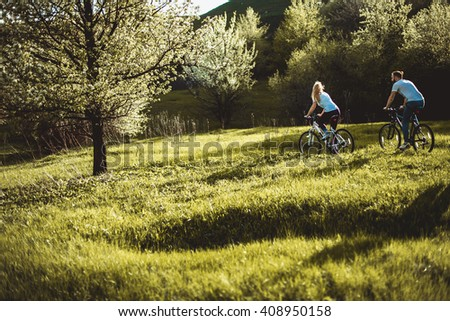 Beautiful young girl and man walking with a bike ride on the green grass. The concept of active rest - stock photo