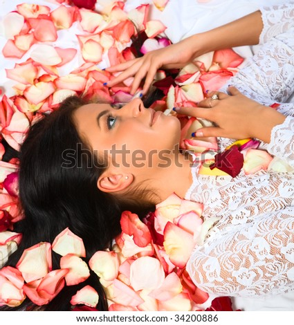 Beautiful young girl and petals of roses