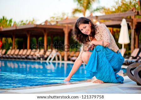 Beautiful young girl at the pool - stock photo