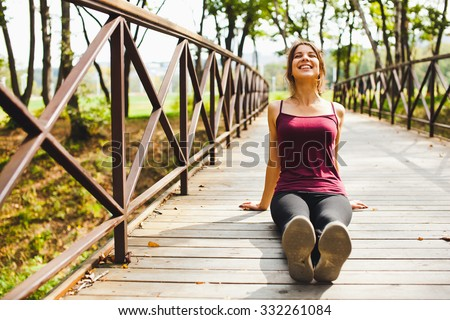 Beautiful young girl athlete on a small bridge in park smiling happy at sunny summer day sitting after run and stretching before training. Getting sunbathes at yoga session. Front view copy space - stock photo