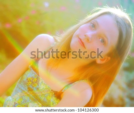 Beautiful young girl bathed in sunlight and rainbow - stock photo
