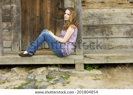 Beautiful young girl.Beautiful curly blonde enjoys the sun in the countryside. Sunrays in the hair. Country style. Country house. perfect weather.