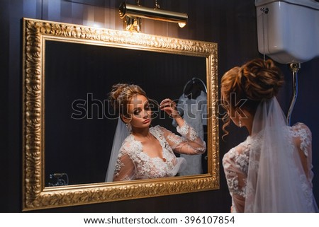 Beautiful young girl bride with fashion wedding hairstyle . Portrait of a young gorgeous bride in wedding white dress with a train , garter , veil , blue eyes . Wedding. - stock photo