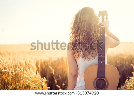 Beautiful young girl carrying her guitar through the golden wheat field. Lens flare, selective focus, toned image. - stock photo