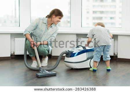 Beautiful young girl cleaning up her house - stock photo