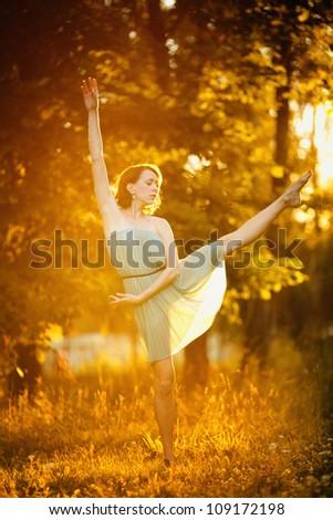 Beautiful young girl dancing in the sun light - stock photo