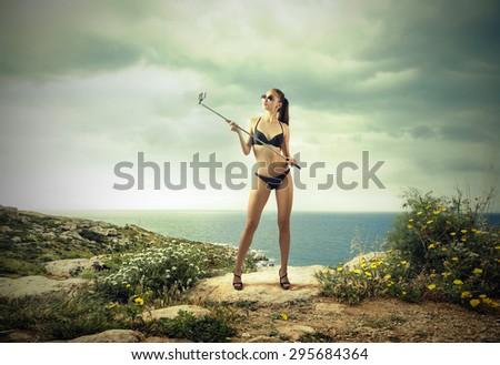 Beautiful young girl doing a selfie - stock photo