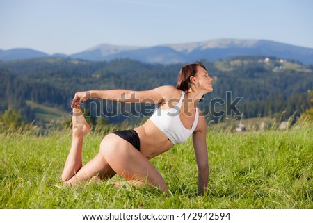 Beautiful young girl doing asana yoga at the summer meadow