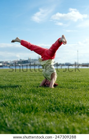 Beautiful young girl doing stretching exercise on green grass. Yoga. Healthy lifestyle.  - stock photo