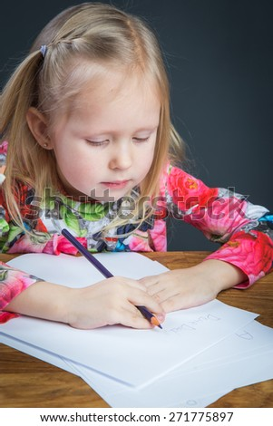 Beautiful young girl drawing with color pencils on a white sheet of paper