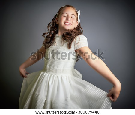 Beautiful young girl dressed in white, dreaming and dancing like a princess. First Communion. Perfect teeth and smile, long curly hair. Dark background, studio shoot. - stock photo