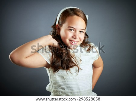 Beautiful young girl dressed in white. First Communion. Perfect teeth and smile, long curly hair, hand in hair. Dark background, studio shoot. - stock photo
