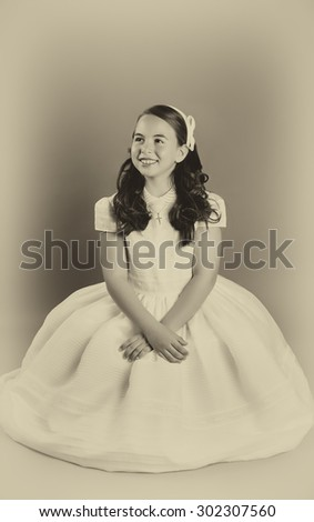 Beautiful young girl dressed in white. First Communion. Perfect teeth and smile, long curly hair, hands folded. Dark background, studio shoot. Sepia picture. - stock photo